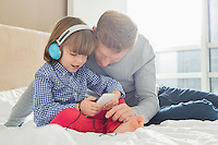 Mid adult father with boy listening music on headphones in bedroom