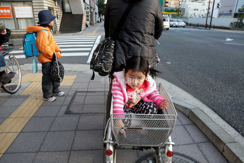 mother riding a bicycle with a child in the back cart