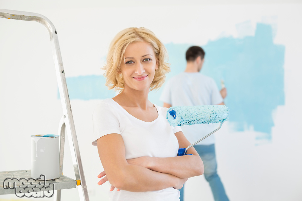 Portrait of woman holding paint roller with man painting wall in background
