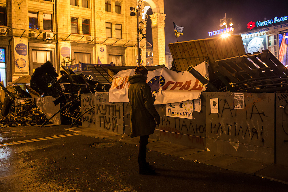 KIEV, UKRAINE - DECEMBER 3: A protester examines graffiti painted on a barricade during a rally in Independence Square on December 3, 2013 in Kiev, Ukraine. Thousands of people have been protesting against the government since a decision by Ukrainian president Viktor Yanukovych to suspend a trade and partnership agreement with the European Union in favor of incentives from Russia. (Photo by Brendan Hoffman/Getty Images) *** Local Caption ***