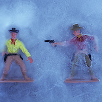 Two plastic models of cowboys in ice with one shooting at the other who is only just drawing his gun