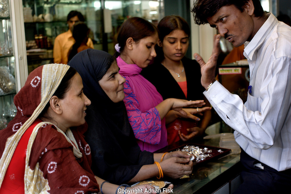 Women and girls look to buy silver rings from a jeweller in Dharavi on 12th Dec 2006. With the slum generating an estimated $800 million to a billion dollars a year business has never been so good.