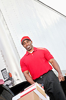 Happy African American delivery man pushing handtruck