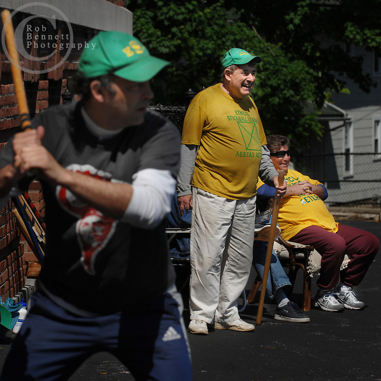 "Andy Ettinger, 49 and an independent bookseller, bats while Howard Weishaus and Jack Dammann watch in the background during a game of stickball..---.The Ethical Stickball League has been operating since 1970, meeting every Sunday in the parking lot behind Hastings High School from 10:30AM to 1PM.  The players are men now mostly in their 70s - carrying nicknames like ""The Wise One"", ""Hit Man"" and ""Plays Hurt"" - who have an affiliation with the school, either as former teachers, students or neighbors. As their slogan suggests, all it takes for a few hours of ""Aestas Aeterna"" (Eternal Summer) is an outside temperature above 45 degrees and 8 willing souls...CREDIT: Rob Bennett for The NY Times"
