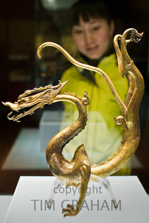 Visitor look at a Chinese dragon ornament on display in glass case in the Shaanxi History Museum, Xian, China