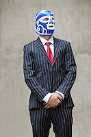 Young businessman in pinstripes suit and wrestling mask looking away over gray background