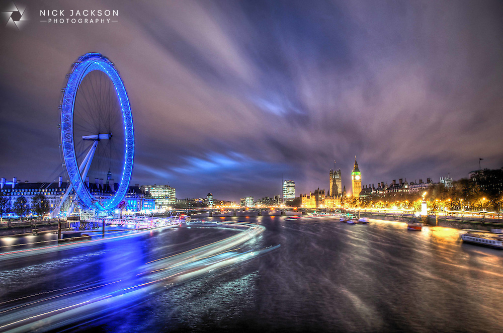 Lights from passenger boats streak up the Thames through the reflection of the London Eye