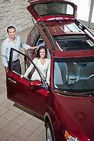 Happy couple in luxury car show room