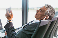 Portrait of mature businessman listening to music on his smartphone while waiting for boarding in airport