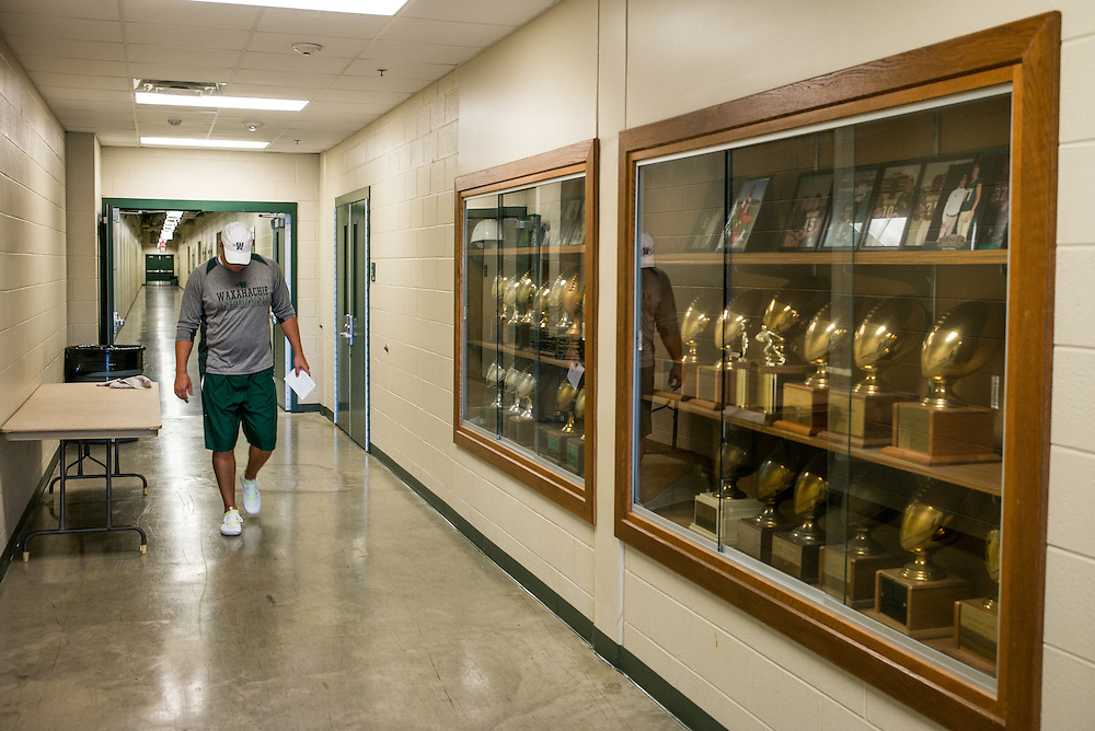 Waxahachie, Texas - September 5, 2015: Jon Kitna, Head Football Coach at Waxahachie High School walks past a trophy case outside the locker room beneath Lumpkins Stadium in Waxahachie, Texas. This is Kitna's first year as head coach at the school. (Darren Carroll for ESPN)