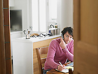 Man sitting in kitchen using phone elevated view