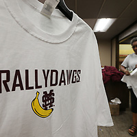 """Louise Givhan begins hanging the new shipment of the """"rally banana"""" shirts for the Mississippi State baseball team as they begin play in Omaha this weekend."""