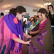 Carrie Pruitt helps Angel Marie Smith learn to hold her shawl and dance during culture class at the Monacan tribal center on Saturday, Feb 6 2016.  Culture class is an opportunity for younger tribal members to learn about making regalia, dancing and traditions from elders. John Boal Photography