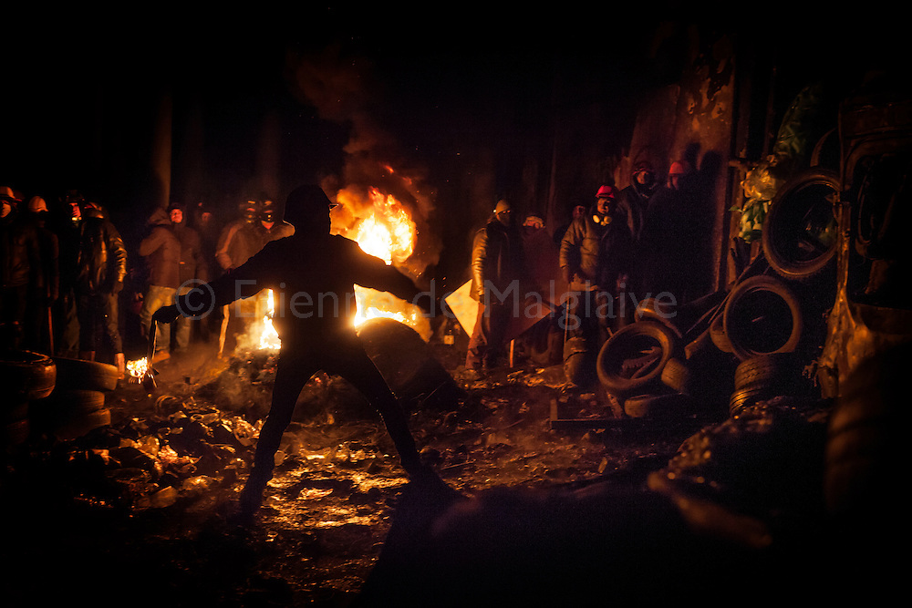 Protester prepares to throw a Molotov cocktail as others keep fueling a fire barricade with tires during clashes  between anti government protesters and riot police on Hrushevskoho street in Kiev. 24 January 2014
