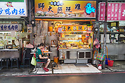 A street food vendor checks her phone while waiting for customers in the early evening at Shida night market. The lanes and alleys that make up the market are filled with street food stalls, boutiques and gift shops.