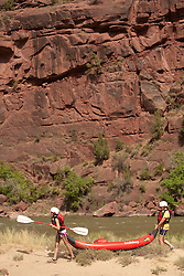 North America, United States, Colorado, Dinosaur National Monument, Green River (Gates of Lodore section), girls carrying kayak in canyon.  MR