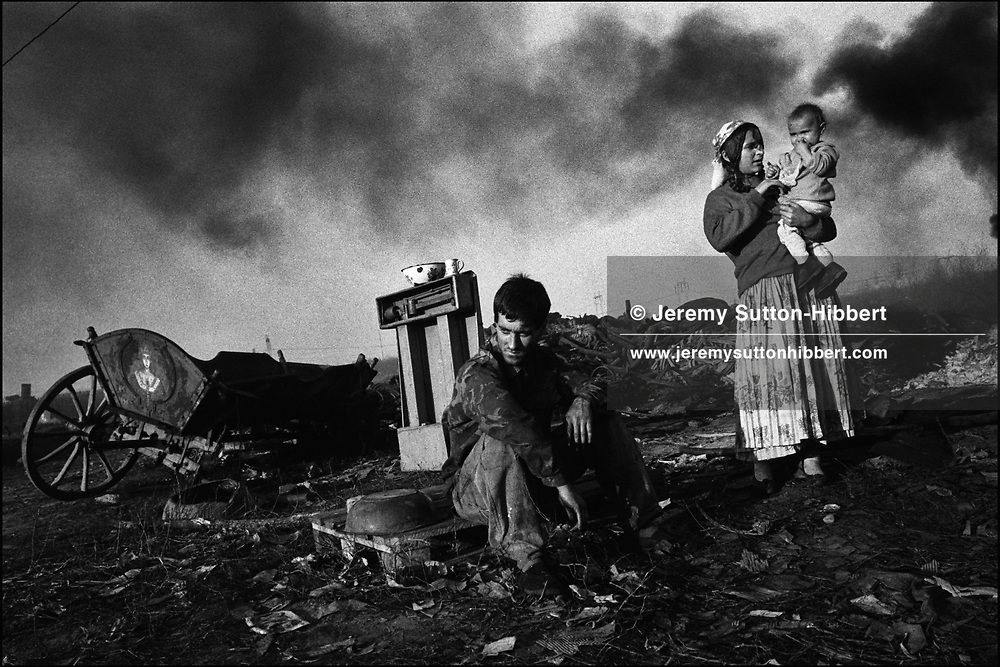 A ROMANIAN EMPLOYED BY THE GYPSIES SITS WAITING FOR SCRAP METAL TO MELT IN A FURNACE. SINTESTI, ROMANIA. NOVEMBER 1996. A Romanian employed by a Kalderash Roma family sits amongst the debris of scrap metal whilst waiting for a furnace to melt other metal, causing all the balck smoke to blow over the Roma camp of Sintesti, near Bucharest.