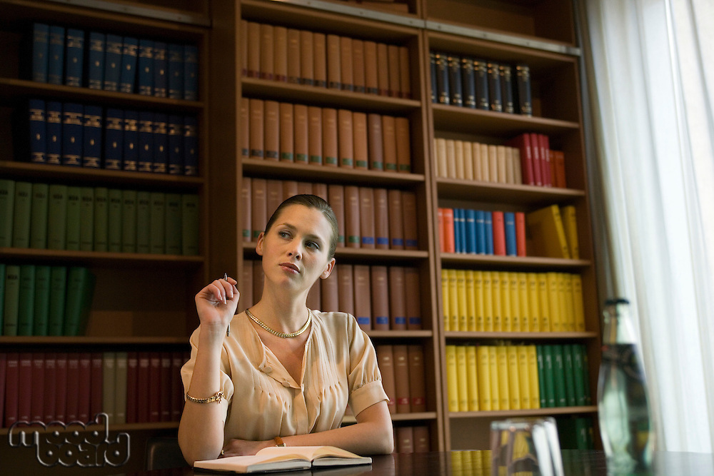 Pensive young woman working at desk in library