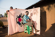 """Irene Sonia, 17, poses in front of a milaya, or bedsheet, in the Bidibidi Refugee Settlement in northwestern Uganda on July 17, 2017. Sonia brought the milaya from her home in South Sudan. """"Life is difficult. My friends are still in South Sudan and I don't even have a phone. I really miss them."""" (photo by Nora Lorek)"""