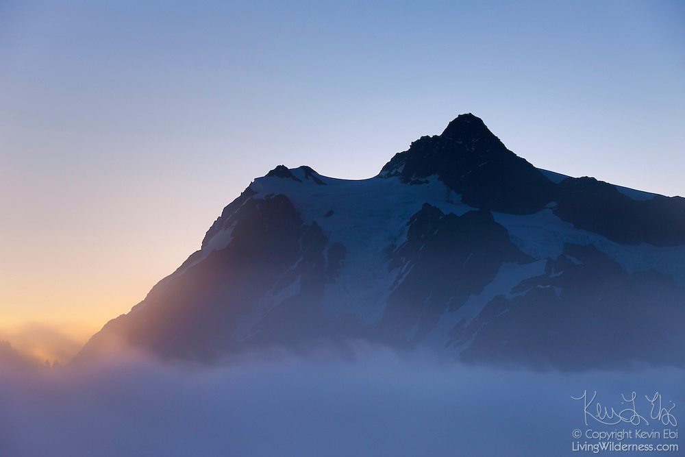 """Mount Shuksan, 9,127-foot (2,782-meter) peak located in the North Cascades National Park in Washington, stands tall over a fog bank. Shuksan is derived from a Skagit Indian word meaning """"rocky and precipitous."""""""