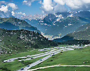 Many hairpin turns climb Pordoi Pass on state highway 48 (Grand Strader delle Dolomiti) from Canazei village, in Val di Fassa (Ladin: Val de Fascia), Dolomites, Italy, Europe. Above the Fassa Valley rises the Rosengarten/Catinaccio Group. Pordoi Pass (or Pordoijoch, 2239 meters/7346 feet) is the highest surfaced road traversing a pass in the Dolomites. The Dolomites are part of the Southern Limestone Alps, in Europe. UNESCO honored the Dolomites as a natural World Heritage Site in 2009.