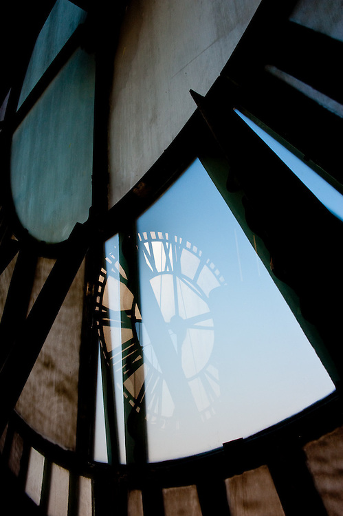 One of the large clock faces reflected in another clock face, viewed from inside the historic Bromo Seltzer Arts Tower in Baltimore.
