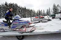 Adam Fisher parks his snowmobile on a trailer after returning from the trail Friday.