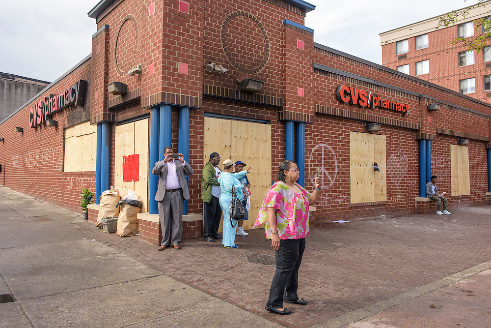 Baltimore, Maryland - April 30, 2015: People make pictures in front of the infamous burned out CVS at the intersection of W. North and Pennsylvania Avenues. Normally this location is a commercial hub in the Sandtown neighborhood of Baltimore, but early last week It became the epicenter for rioting the day Freddie Gray was put to rest Monday. The CVS was looted and burned, a check cashing business was broken in to, three police vehicles were destroyed, two were set on fire. Community relations with police have been hostile for decades. When Former Maryland Governor Martin O'Malley was mayor he enacted a zero tolerance policy to reduce crime. The tactic worked, but increased prison population, and gave many residents of Sandtown records with long rap sheets of both minor and major infractions, driving up debt while making them unemployable. <br /> <br /> The poor, predominately black area of Baltimore known as Sandtown is where the most violent riots occurred the week Freddie Gray was laid to rest. Tensions between the are's residents and police have been bubbling long before Freddie Gray died while in police custody. <br /> <br /> CREDIT: Matt Roth for The Globe and Mail