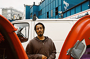 Man standing in carpark, Chariot Spa, Fairchild St., Shoreditch, London May 2016.