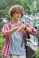 Young male hiker checking the time in forest