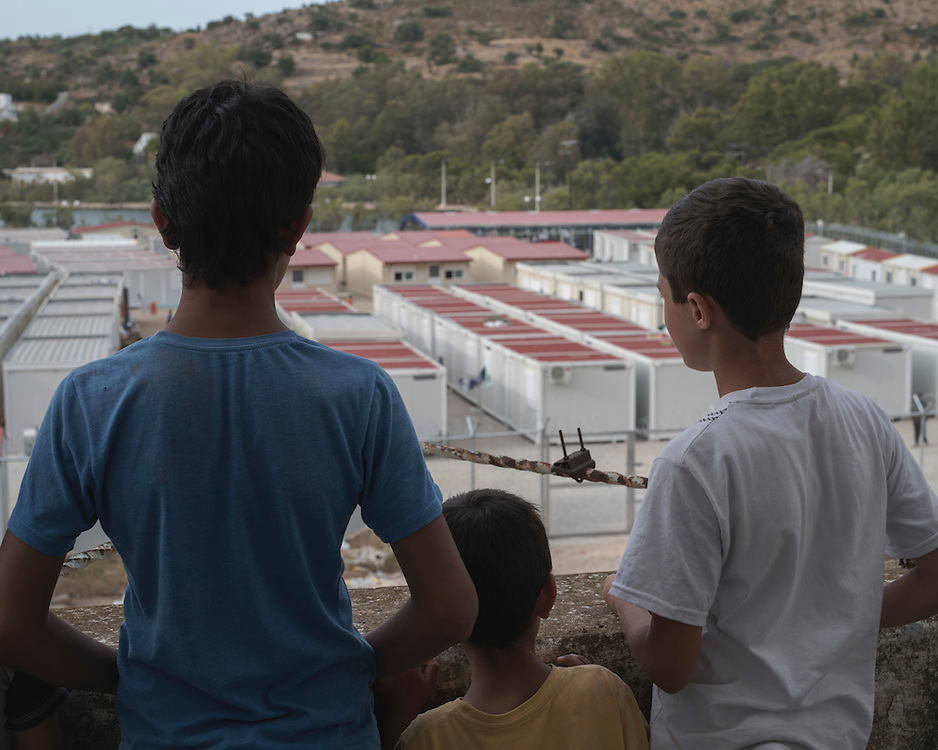 Three refugee children, Youssef, 14, Rebas, 9, and Diar, 13, looking over the Leros 'Hotspot', an EU-run migrant's reception centre opened in the grounds of the former Lepida psychiatric hospital. <br />