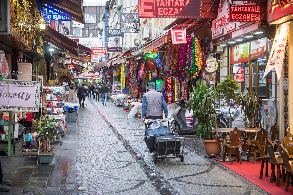 A man pulls a hand truck carrying luggage down a street lined with various shops selling goods,  Istanbul, Turkey