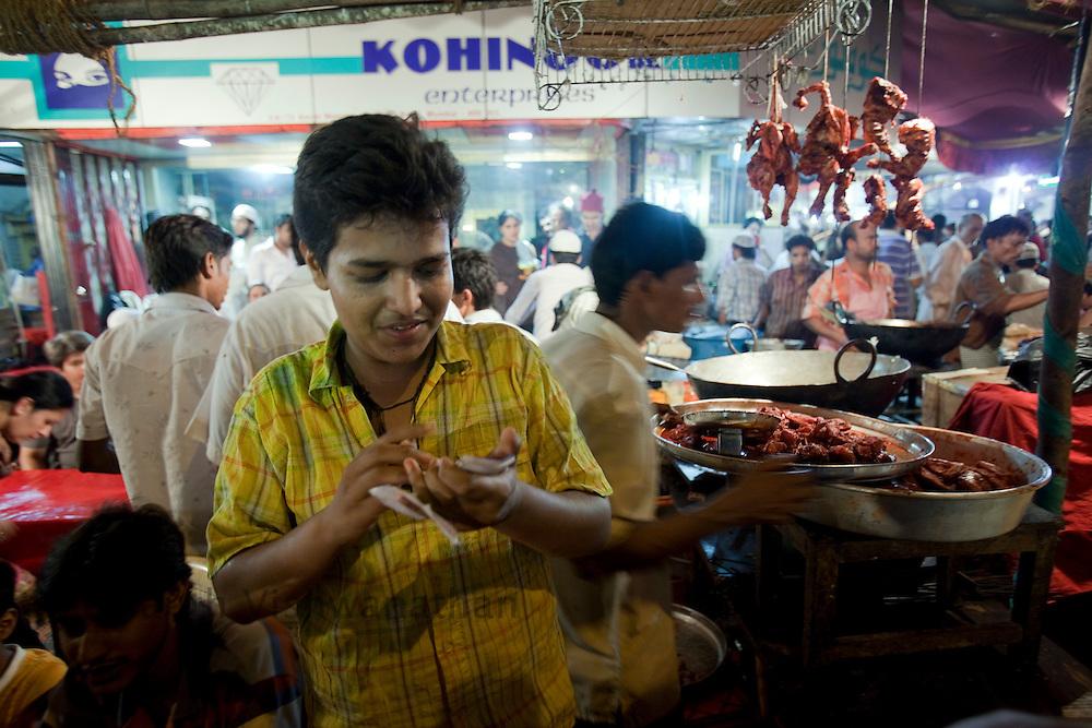 Abdul Rehman calcuates customer bills at the largets food stall, opposite Minara masjid at Mohammed Ali road in Mumbai, Maharashtra, India, on Saturday September 6, 2009. Photographer: Prashanth Vishwanathan/The National