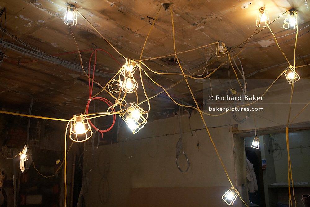 A tangle of electric lights are strung together on the ceiling of a West End construction site in London's Soho.