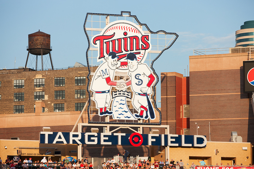 """Minneapolis, USA - July 18, 2011: Minnie and Paul logo in the outfield at Target Field in Minneapolis. A large version of the Twins' original """"Minnie and Paul"""" logo (designed by local artist, Ray Barton) stands in center field. It shows two players wearing the uniforms of the two minor-league teams that played in the Twin Cities before the Twins' arrival, the Minneapolis Millers and St. Paul Saints, shaking hands across the Mississippi River. During various points in the game, the strobe lights surrounding the logo flash"""