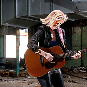 A 42-year-old woman with blonde hair wearing a black leather pants and a black button-down shirt  plays a Taylor guitar in an abandoned old mill in the Haw River Township in NC.