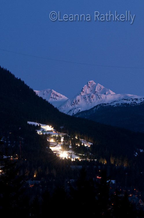 The Whistler Sliding Centre hosts the skeleton, luge and bobsleigh events during the 2010 Olympic Winter Games in Whistler, BC Canada. Here, the sliding centre is brightly lit during an olympic event at night, and Fissile Mountain rises above, with the Peak to Peak gondola line just visible.
