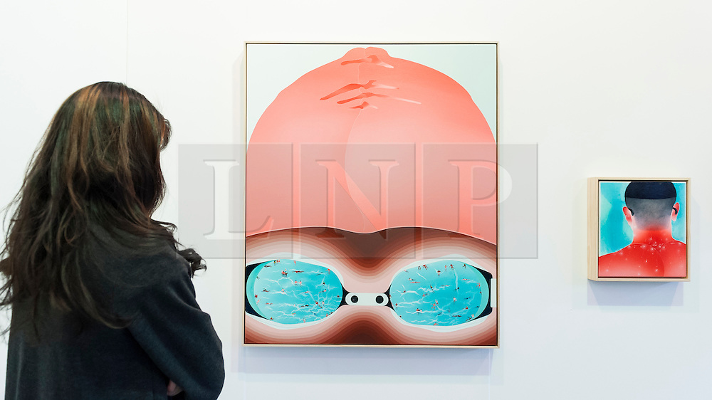 "© Licensed to London News Pictures. 19/05/2016. London, UK. A visitor views Fan Yan-Tsung's (L to R) ""Gaze"" and ""Bowl Cut"".  Art16 opens at Olympia, in west London.  Now in its fourth edition, the fair brings together over 100 galleries from more than 30 countries showcasing a diverse cross-section of work by contemporary artists from around the world for buyers and art enthusiasts to visit. Photo credit : Stephen Chung/LNP"