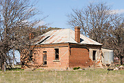 Dilapidated rundown old brick farm house in paddock near Molong, New South Wales, Australia
