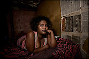 """Sennait, 21 years old, lies on the bed in her shack. She at the age of 8 years is sold in marriage to a man. After an initial period spent with the mother, leaves his village to live with her husband. Already by the first week begins the first sexual abuse. With the help of a friend managed to flee home. By that time had no more news about her husband. Addis Ababa, Ethiopia, on thursday, Febrary 19 2009.....In a tangled mingling of tradition and culture, in the normal place of living, in a laid-back attitude. The background of Ethiopia's """"child brides"""", a country which has the distinction of having highest percentage in the practice of early marriages despite having a law that establishes 18 years as minimum age to get married. Celebrations that last days, their minds clouded by girls cups of tella and the unknown for the future. White bridal veil frame their faces expressive of small defenseless creatures, who at the age ranging from three to twelve years shall be given to young brides men adults already...To protect the identities of the recorded subjects names and specific places are fictional."""