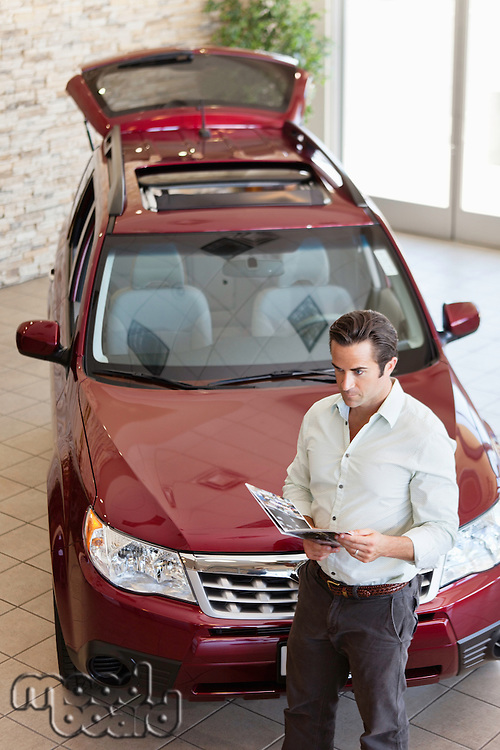 Mid-adult man reading document in front of luxury car in show room