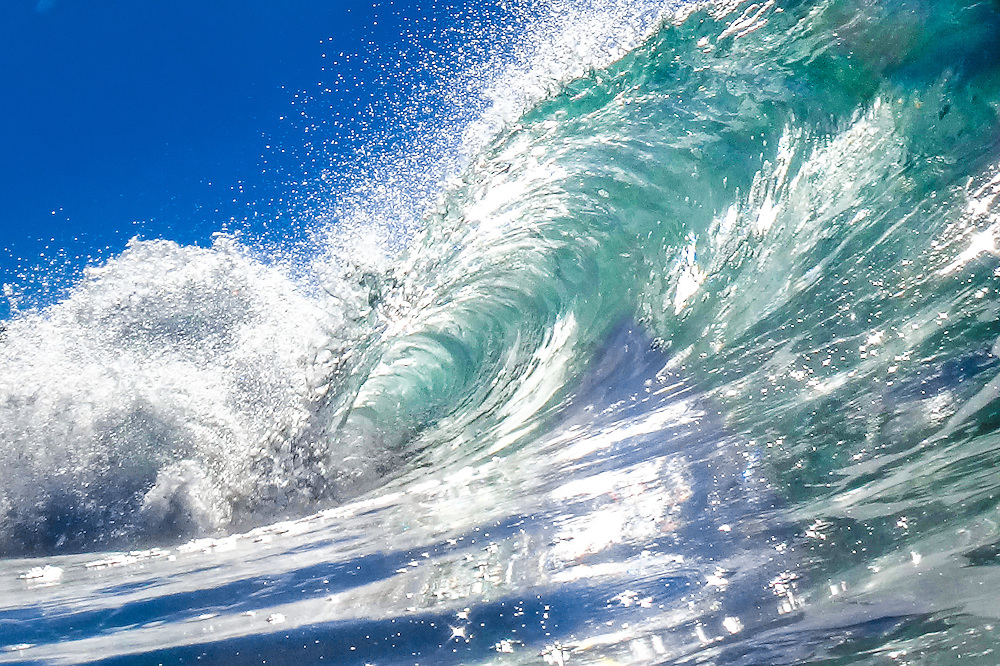 Photographic art design of the inside of a breaking wave sparkling ing the morning sun.
