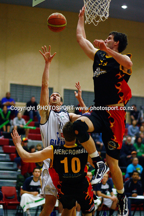 Giants' Tony Rampton charges into Pistons' Thomas Abercrombie as Alex Pledger looks to block the shot. Bartercard NBL Semifinal, Waikato Pistons v Nelson Giants, Hamilton Boys High School, Hamilton, New Zealand. Friday 25th June 2010. Photo: Anthony Au-Yeung/PHOTOSPORT