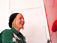 young girl painting a wall red with a roller