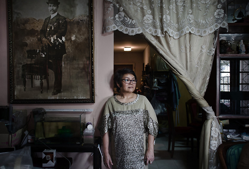 April 2013 - Mrs Suporn Rujapan stands in her living room next to the &quot;King Rama V&quot; portrait. The paint shows the level reached by the water during the flood in the area. She stayed in her home for the entire duration of the flood. After initially finding herself a victim of the disaster, she quickly grew into a role as front-line leader of her community&rsquo;s relief efforts, directing government and volunteer resources and becoming a minor media celebrity in the process.<br /> Muang Aek, north west Bangkok. &copy; Giorgio Taraschi for The Rockefeller Foundation/Next City