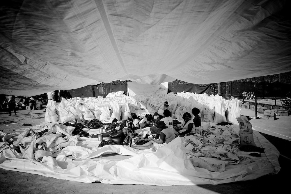 Families sit in the shade under a tarp surrounded by food provided by USAID after the recent earthquake in Port-au-Prince, Haiti.