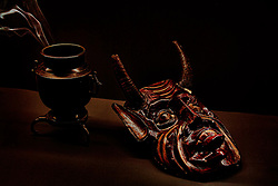 A stylized portrait of a devil mask from northern Mexico and a bronze Japanese urn set on a black background.