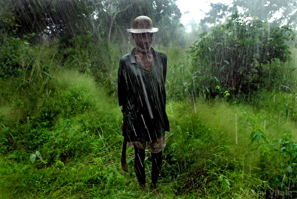 A Tanzanian walks from his field near sunset in the village of Simana. The dense forest and tall grasses make villagers vulnerable to lion attacks. They have to stay late in the evening in their fields to protect their crops from rampaging monkeys who like to eat the rice and corn, forcing them to walk at sunset, the time of day when lions are out looking for prey.  Ami Vitale