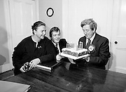 An Taoiseach Dr Garret FitzGerald TD blows out the candles on his fifty-sixth birthday cake, watched by his wife Joan and son Mark.<br />