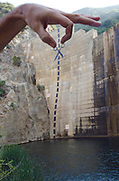 A hand posing with scissors and cut marks painted on the obsolete Matilija Dam in Los Padres National Forest near Ojai, California.